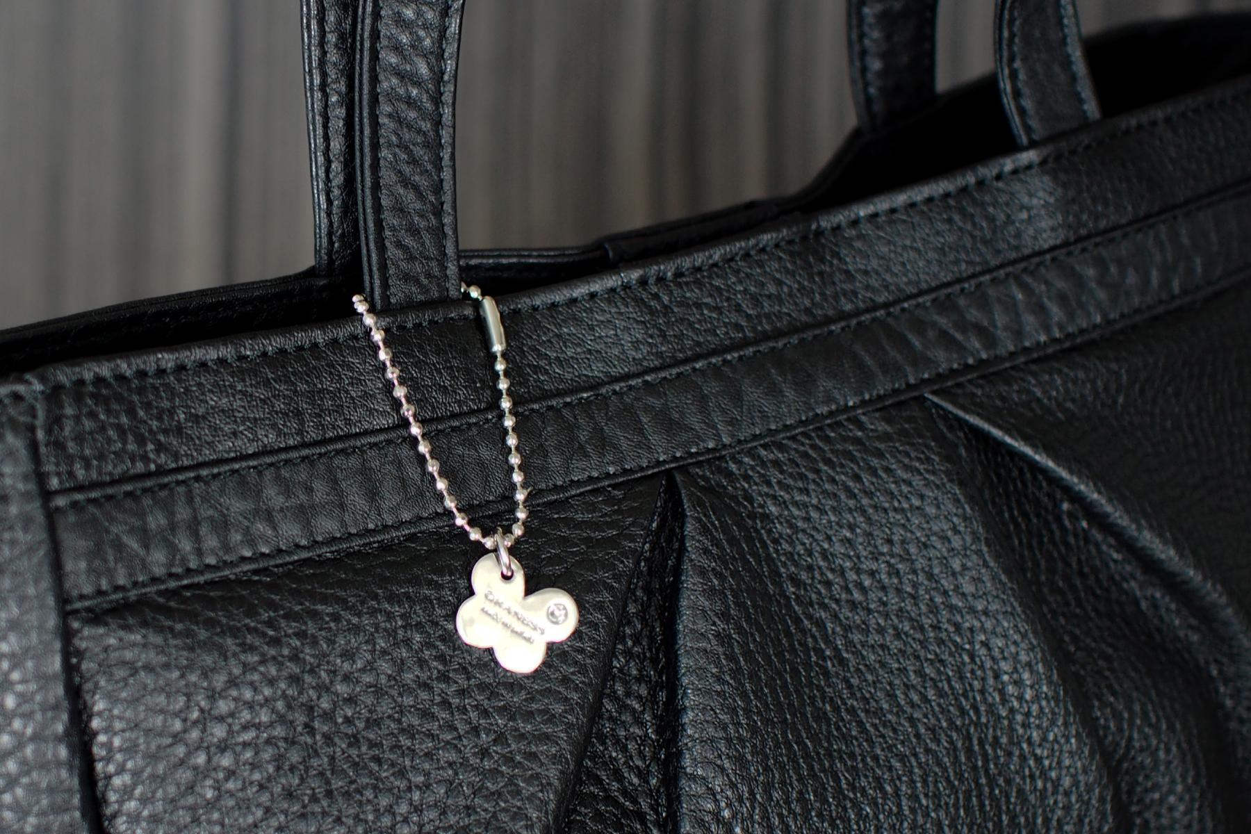 の女性に人気のチャームを本革製バッグ・ドレープトートに取り付けたイメージ
